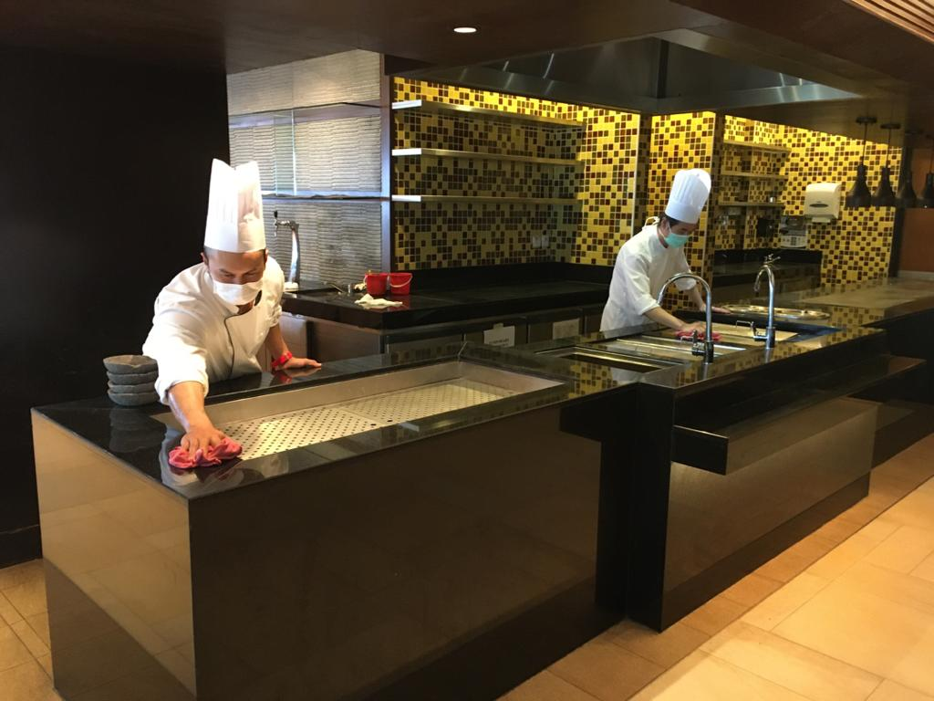 Chefs cleaning the kitchen and dining areas.